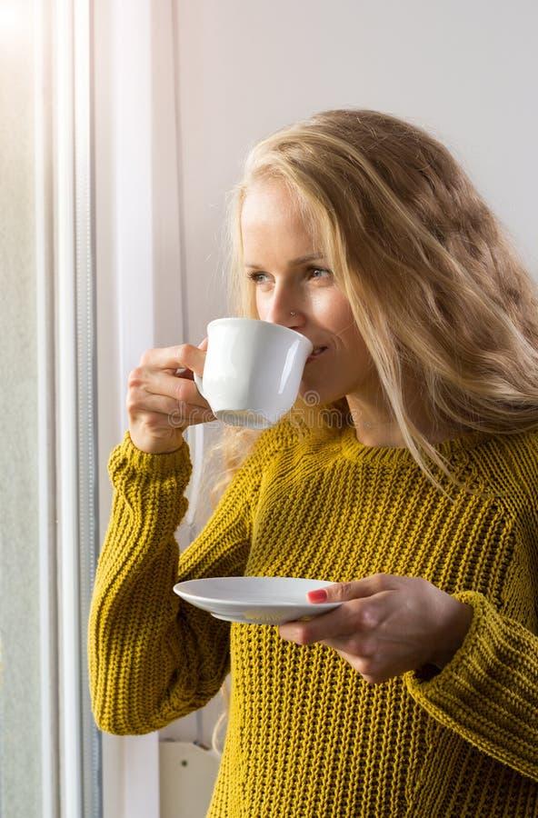 Καφές κατανάλωσης γυναικών εκτός από το παράθυρο στοκ εικόνες