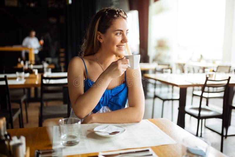 Καφές κατανάλωσης γυναικών στο εστιατόριο στοκ εικόνα
