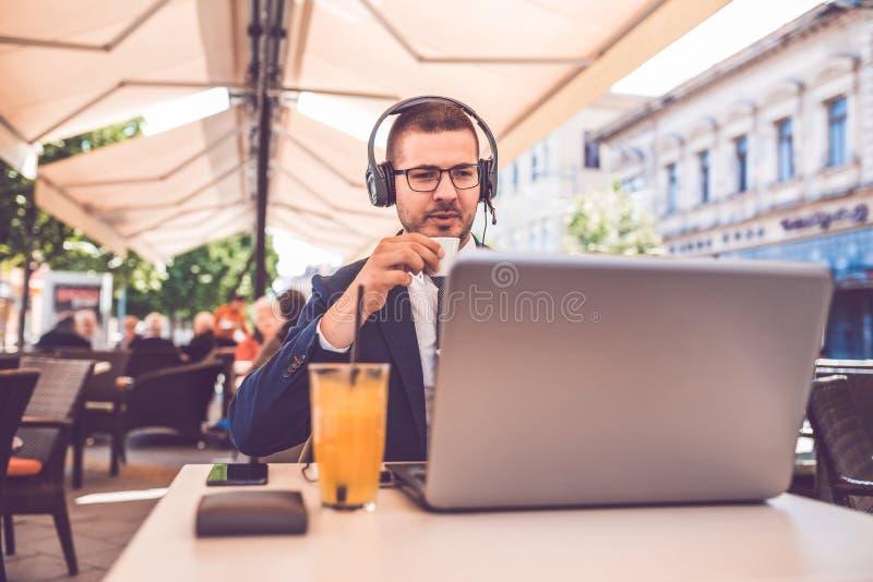 Καφές κατανάλωσης νεαρών άνδρων ενώ έχοντας μια συνομιλία σε μια φθορά lap-top ακουστικά στοκ εικόνα με δικαίωμα ελεύθερης χρήσης