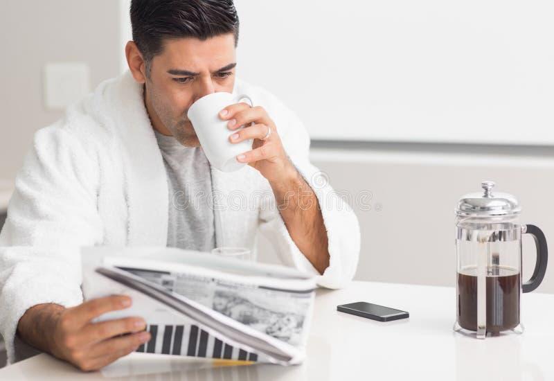 Καφές κατανάλωσης ατόμων διαβάζοντας την εφημερίδα στην κουζίνα στοκ φωτογραφία