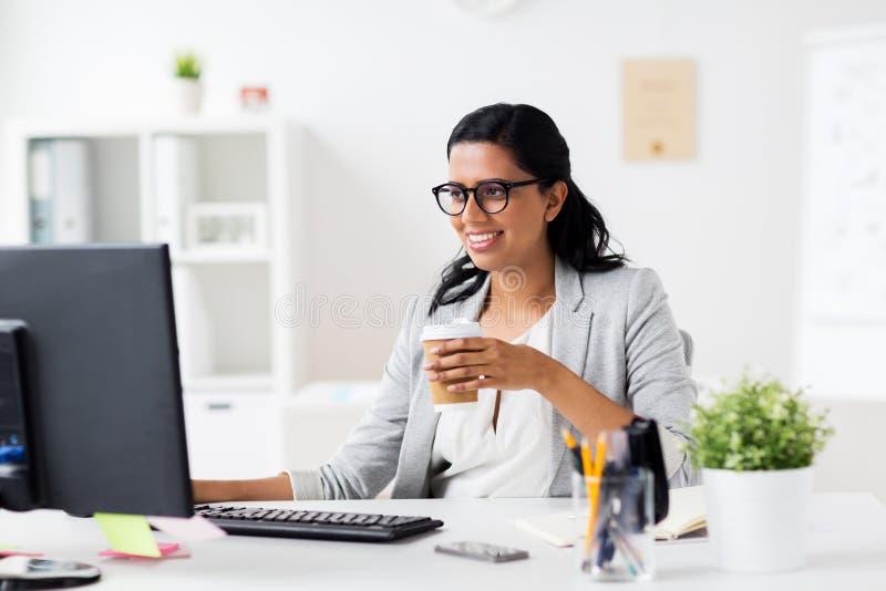 Καφές κατανάλωσης επιχειρηματιών στον υπολογιστή γραφείων στοκ εικόνα με δικαίωμα ελεύθερης χρήσης