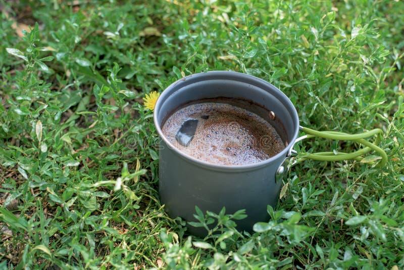 Καφές με τον αφρό που παρασκευάζεται σε ένα φλυτζάνι στρατόπεδων γκρίζου στη φύση οι στάσεις φλυτζανιών στοκ εικόνες