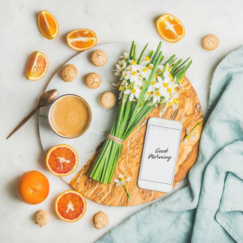 Καφές, μπισκότα, πορτοκάλια, λουλούδια και κινητό τηλέφωνο με τη καλημέρα στοκ φωτογραφία με δικαίωμα ελεύθερης χρήσης