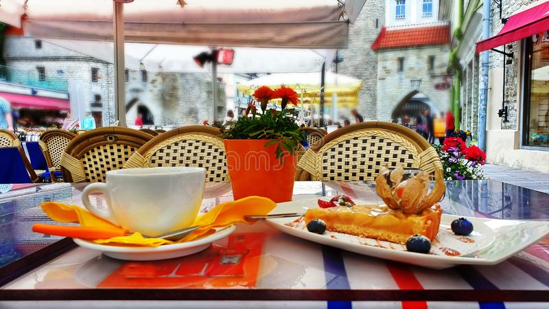 Καφές οδών στην παλαιά πόλη του ταξιδιού του Ταλίν στον πίνακα καφετερίων της Εσθονίας στο τοπ κέικ μήλων φλιτζανιών του καφέ και στοκ φωτογραφία
