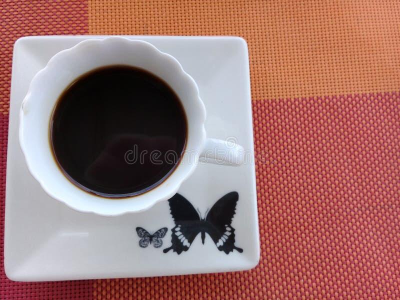 Καφές πάνω από ένα πιατάκι με το σχέδιο πεταλούδων στοκ φωτογραφία με δικαίωμα ελεύθερης χρήσης
