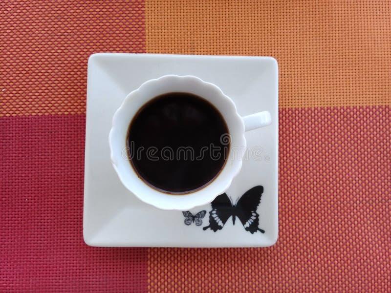 Καφές πάνω από ένα πιατάκι με το σχέδιο πεταλούδων στοκ εικόνες