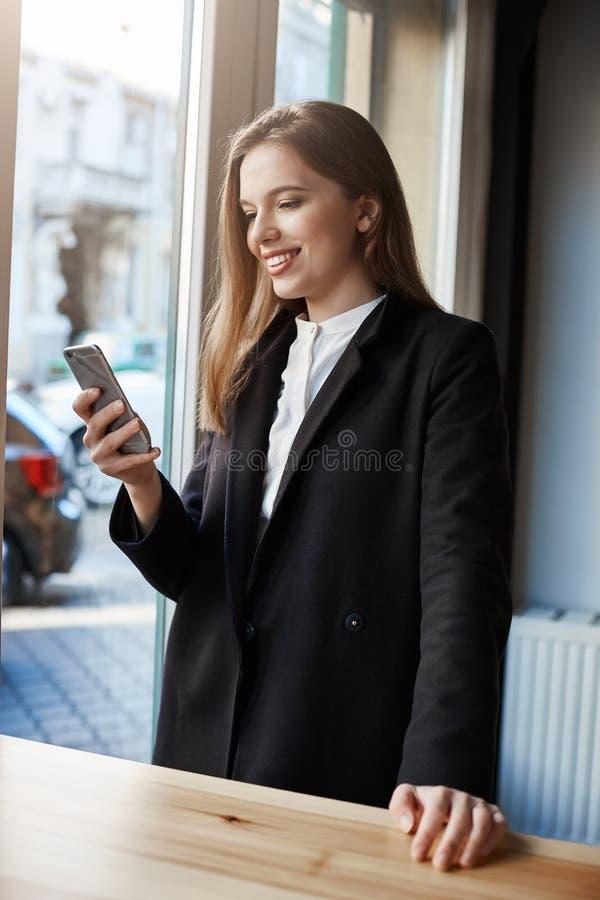 Καφές πριν από την επιχείρηση Πορτρέτο της μοντέρνης επιτυχούς αστικής στάσης γυναικών κοντά στο μετρητή καφέδων, που περιμένει τ στοκ φωτογραφία