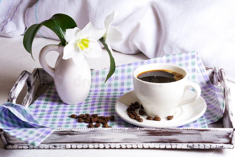 Καφές πρωινού στο κρεβάτι με τα άσπρα λουλούδια κρίνων στοκ εικόνες