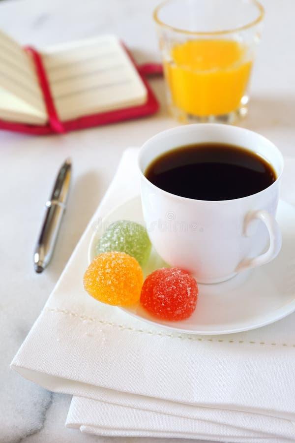 Καφές πρωινού, χυμός από πορτοκάλι, καραμέλα gummi και σημειωματάριο στοκ φωτογραφία με δικαίωμα ελεύθερης χρήσης