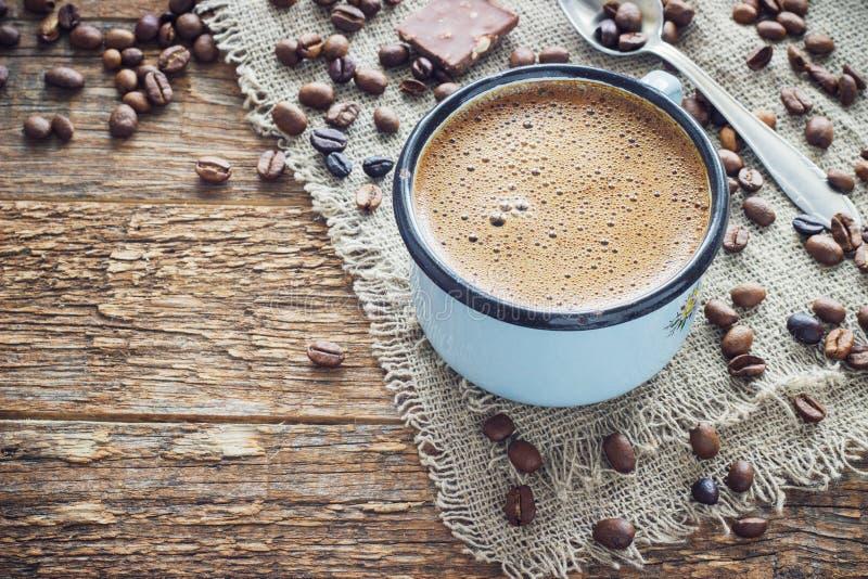 Καφές σε μια κούπα μετάλλων στο παλαιό ξύλινο υπόβαθρο με τα σιτάρια στοκ εικόνες