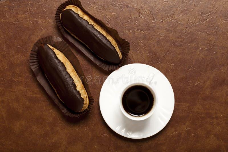 Καφές, σοκολάτα ECLAIR, καφές σε ένα άσπρο φλυτζάνι, άσπρο πιατάκι, σε έναν στοκ εικόνες
