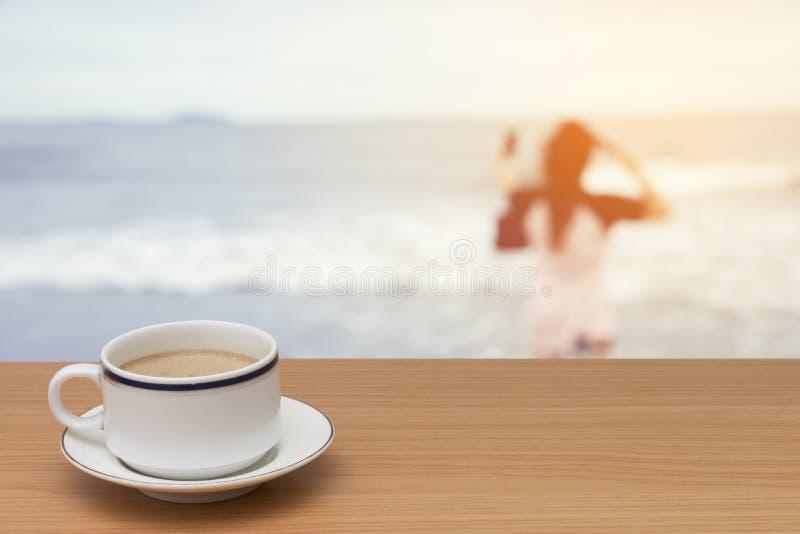Καφές στον ξύλινο πίνακα με το θολωμένο υπόβαθρο της γυναίκας στο β στοκ εικόνα με δικαίωμα ελεύθερης χρήσης