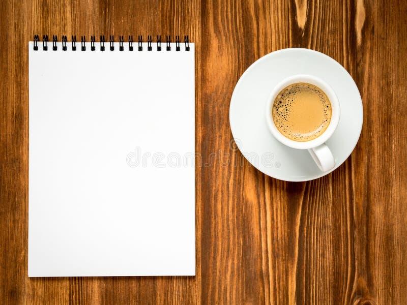 Καφές στο άσπρο φλυτζάνι και ανοικτό σημειωματάριο με μια καθαρή άσπρη σελίδα στοκ φωτογραφία με δικαίωμα ελεύθερης χρήσης