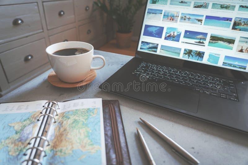 Καφές στο συγκεκριμένο πίνακα με το χάρτη, τις μάνδρες και το lap-top ταξιδιού με τους προορισμούς ταξιδιού ως σκηνικό στοκ φωτογραφίες με δικαίωμα ελεύθερης χρήσης