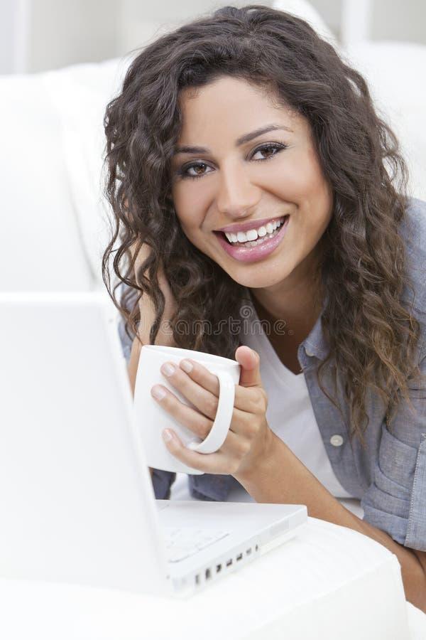 Καφές τσαγιού κατανάλωσης γυναικών που χρησιμοποιεί το φορητό προσωπικό υπολογιστή στοκ φωτογραφία με δικαίωμα ελεύθερης χρήσης