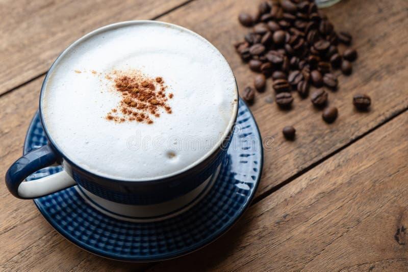 Καφές Capucino με τα φασόλια καφέ στον παλαιό ξύλινο πίνακα στοκ φωτογραφία με δικαίωμα ελεύθερης χρήσης