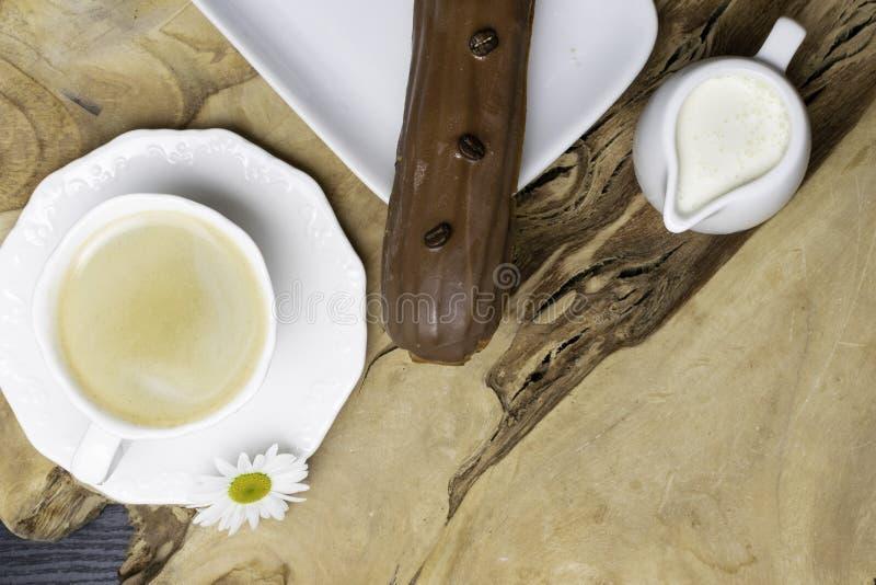 Καφές eclairs με το φλυτζάνι του φρέσκου μαύρου καφέ στον ξύλινο πίνακα, chamomile λουλούδι Τοπ όψη στοκ φωτογραφία με δικαίωμα ελεύθερης χρήσης