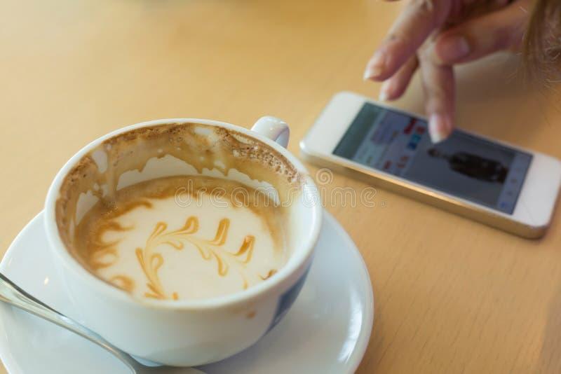 Καφές macchiato καραμέλας και χέρι γυναικών που χρησιμοποιούν ένα κινητό τηλέφωνο στοκ εικόνες με δικαίωμα ελεύθερης χρήσης