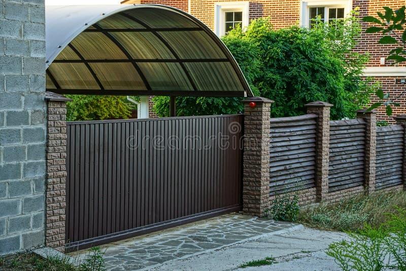 Καφετής ξύλινος φράκτης και κλειστές πύλες με ένα ιδιωτικό σπίτι κοντά στο δρόμο στοκ εικόνα