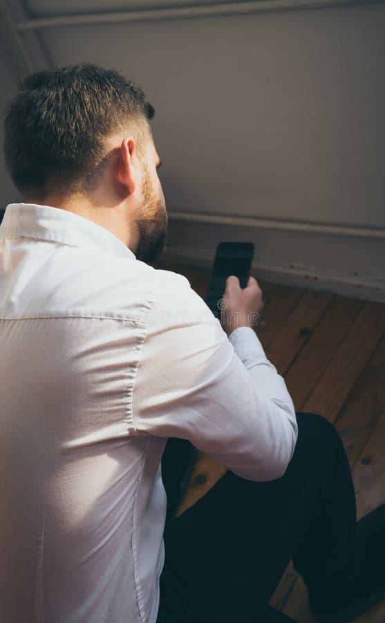 Καφετής τουρκικός τύπος τρίχας κομψός στην άσπρη συνεδρίαση πουκάμισων στο κρεβάτι του που ελέγχει τα μηνύματα ανάγνωσης smartpho στοκ εικόνες