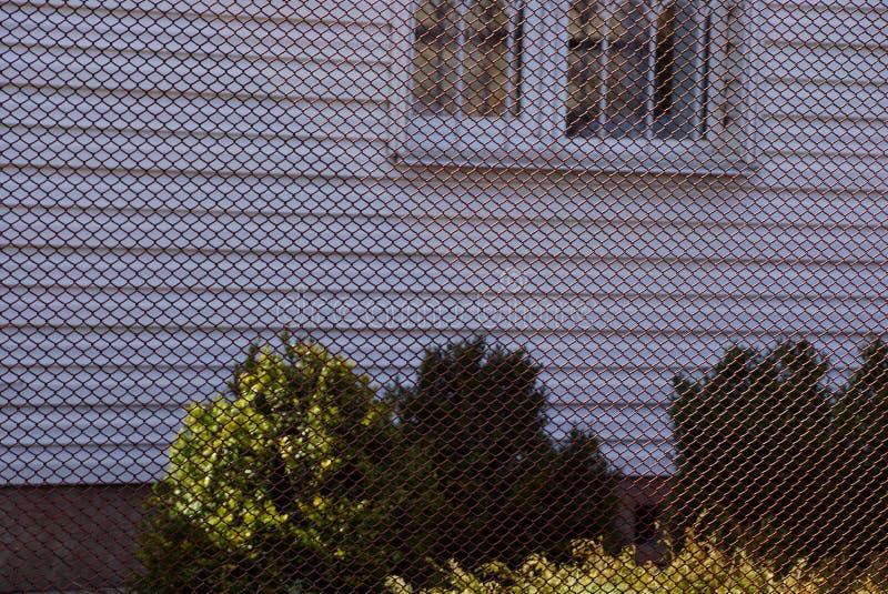 Καφετής φράκτης πλέγματος μετάλλων μπροστά από τον τοίχο του σπιτιού με ένα παράθυρο και πράσινους θάμνους στοκ εικόνες