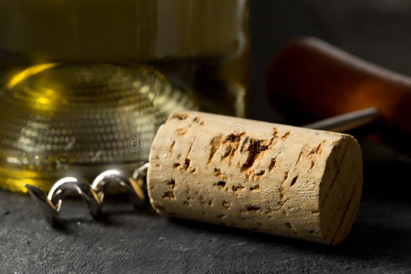 Καφετής φυσικός φελλός κρασιού με το ανοιχτήρι και το μπουκάλι του άσπρου κρασιού στοκ εικόνες