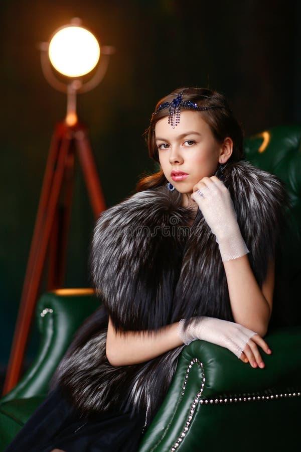 Καφετής-eyed κορίτσι σε μια φανέλλα γουνών και γάντια με το εξάρτημα στο χ του στοκ φωτογραφία με δικαίωμα ελεύθερης χρήσης