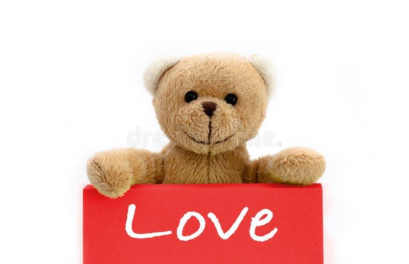 """Καφετής teddy αγάπης αντέχει με τα δύο χέρια που ένα κόκκινο ρόδινο χρώμα σημειώνει με το μήνυμα """"Love ` στοκ φωτογραφίες"""