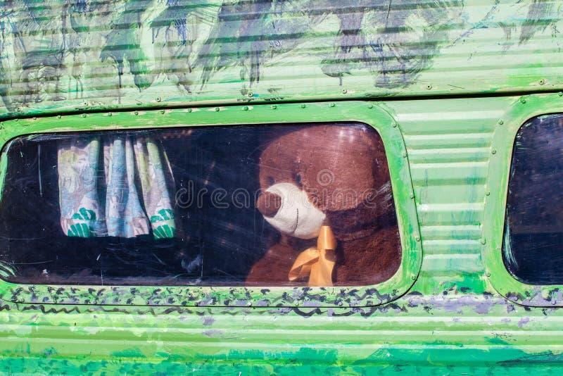 Καφετής teddy αντέχει από το αναδρομικό χρωματισμένο παράθυρο τροχόσπιτων στοκ φωτογραφία