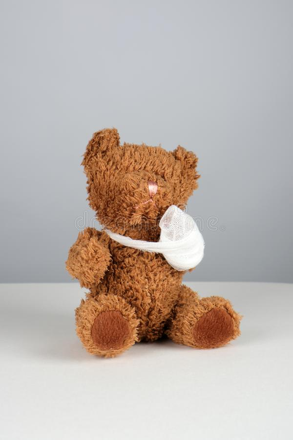 καφετής teddy αντέχει με ένα επιδεμένο πόδι στοκ φωτογραφία