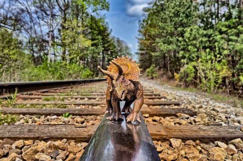 Καφετής triceratops δεινόσαυρος που περπατά στις διαδρομές σιδηροδρόμου στοκ εικόνα με δικαίωμα ελεύθερης χρήσης