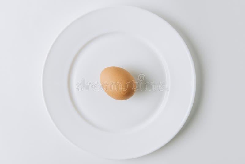 καφετί αυγό που βάζει στο άσπρο πιάτο στοκ φωτογραφίες με δικαίωμα ελεύθερης χρήσης