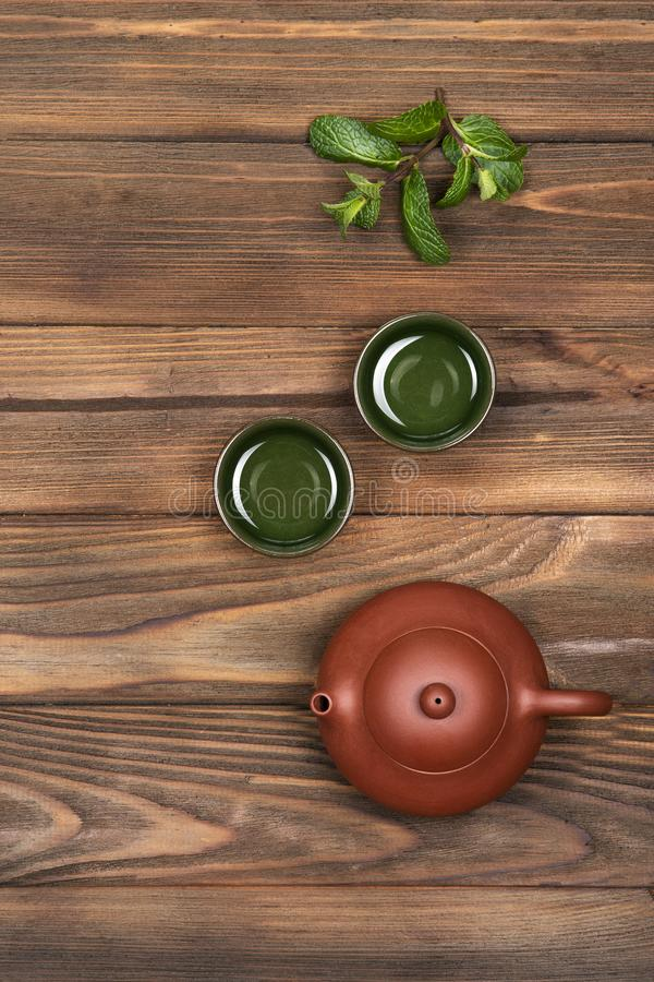 Καφετί κεραμικό teapot, δύο σκούρο πράσινο μικρά ειδικά φλυτζάνια και η φρέσκια μέντα σκοτεινό σε έναν ξύλινο το υπόβαθρο Τελετή  στοκ φωτογραφία με δικαίωμα ελεύθερης χρήσης