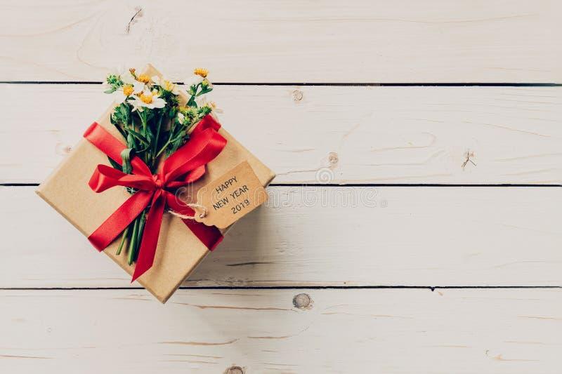 Καφετί κιβώτιο δώρων με την ετικέττα καλή χρονιά 2019 στο ξύλινο υπόβαθρο W στοκ φωτογραφία με δικαίωμα ελεύθερης χρήσης