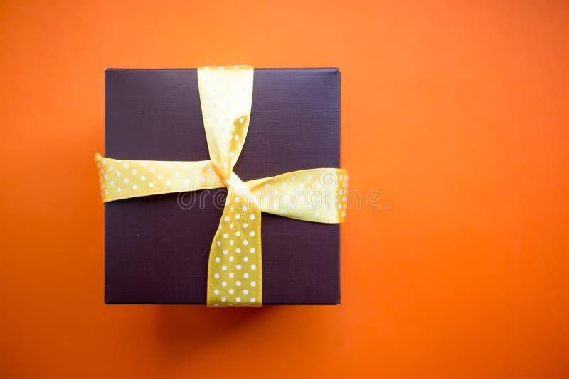 Καφετί κιβώτιο δώρων με την κίτρινη κορδέλλα στο πορτοκαλί υπόβαθρο Τοπ άποψη με το διάστημα αντιγράφων στοκ εικόνα με δικαίωμα ελεύθερης χρήσης