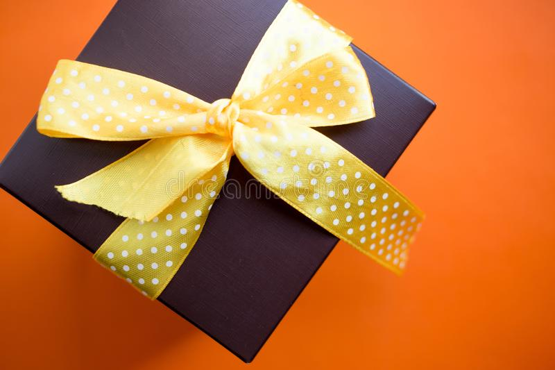 Καφετί κιβώτιο δώρων με την κίτρινη κορδέλλα στο πορτοκαλί υπόβαθρο Τοπ άποψη με το διάστημα αντιγράφων στοκ εικόνα