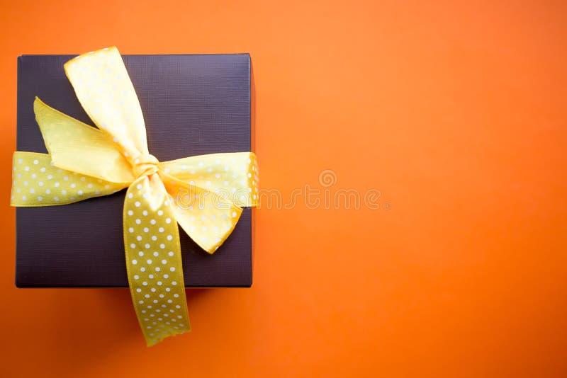 Καφετί κιβώτιο δώρων με την κίτρινη κορδέλλα στο πορτοκαλί υπόβαθρο Τοπ άποψη με το διάστημα αντιγράφων στοκ εικόνες