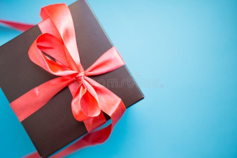 Καφετί κιβώτιο δώρων με την κόκκινη κορδέλλα στο μπλε υπόβαθρο Τοπ άποψη με το διάστημα αντιγράφων στοκ φωτογραφίες με δικαίωμα ελεύθερης χρήσης