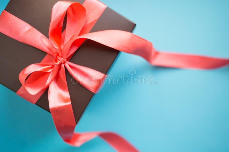 Καφετί κιβώτιο δώρων με την κόκκινη κορδέλλα στο μπλε υπόβαθρο Τοπ άποψη με το διάστημα αντιγράφων στοκ φωτογραφία