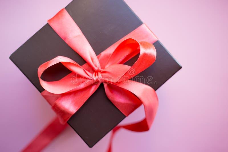 Καφετί κιβώτιο δώρων με την κόκκινη κορδέλλα στο ρόδινο υπόβαθρο Τοπ άποψη με το διάστημα αντιγράφων στοκ φωτογραφία με δικαίωμα ελεύθερης χρήσης
