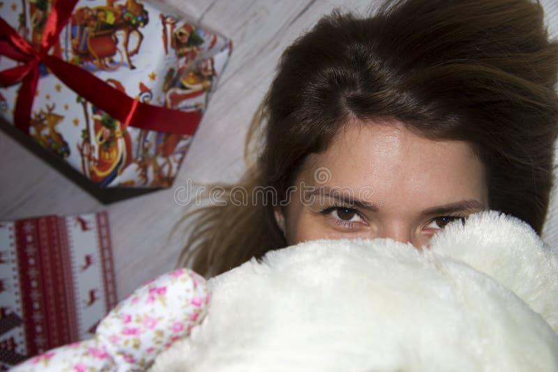 Καφετί κορίτσι τρίχας με τη teddy αρκούδα που κοιτάζει στα μάτια σας κοντά στοκ εικόνες