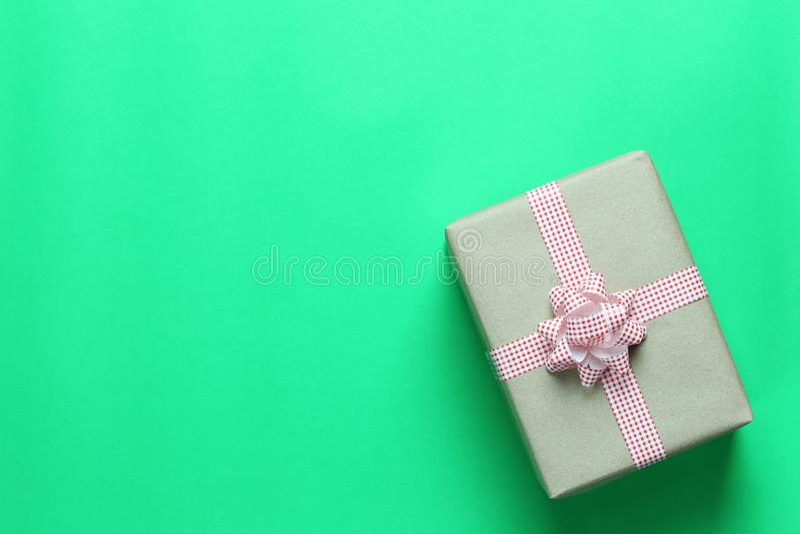 Καφετί πεδίο δώρων Χριστουγέννων που τοποθετείται σε ένα πράσινα πάτωμα εγγράφου τέχνης και ένα χ στοκ φωτογραφίες