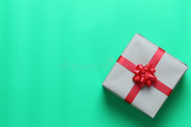 Καφετί πεδίο δώρων Χριστουγέννων που τοποθετείται σε ένα πράσινα πάτωμα εγγράφου τέχνης και ένα χ στοκ εικόνες