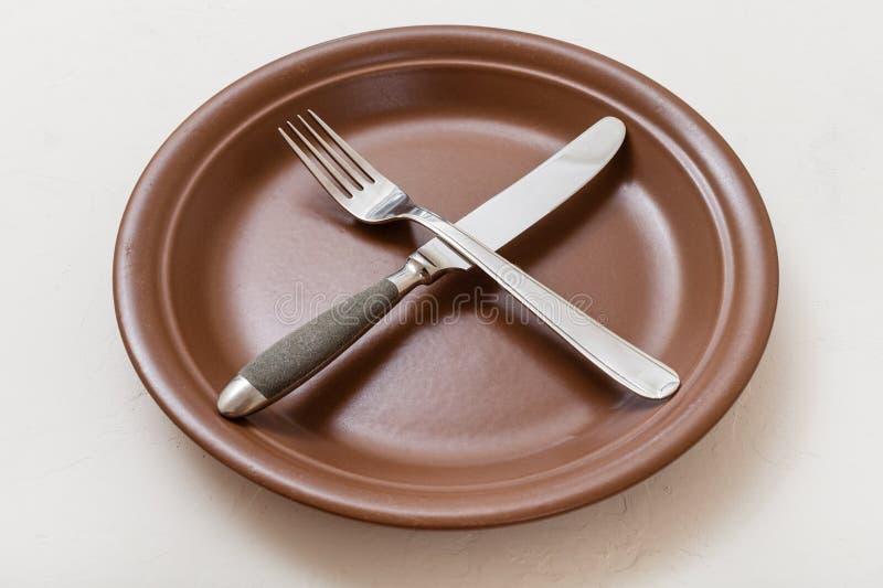 Καφετί πιάτο με το πέρασμα του μαχαιριού, κουτάλι στο λευκό στοκ φωτογραφίες