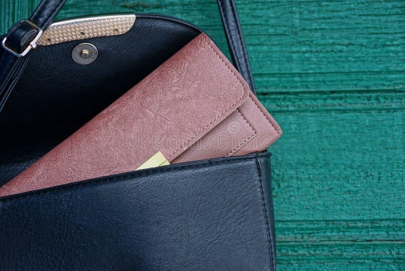 Καφετί πορτοφόλι σε μια ανοικτή μαύρη τσάντα δέρματος στον πράσινο τοίχο στοκ φωτογραφία με δικαίωμα ελεύθερης χρήσης