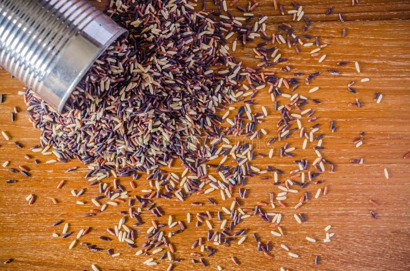 καφετί ρύζι από το δοχείο κασσίτερου στον ξύλινο πίνακα στοκ φωτογραφίες με δικαίωμα ελεύθερης χρήσης