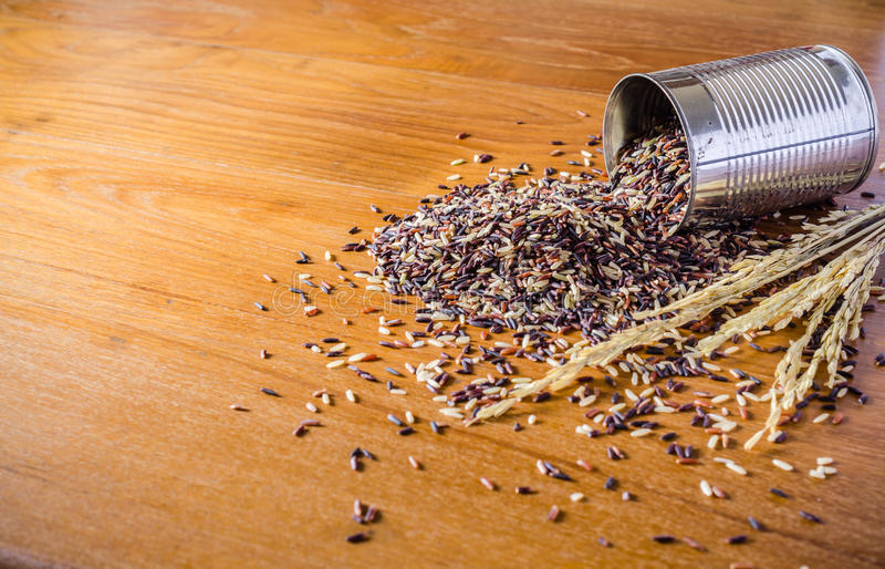 καφετί ρύζι από το δοχείο κασσίτερου στον ξύλινο πίνακα στοκ φωτογραφία με δικαίωμα ελεύθερης χρήσης
