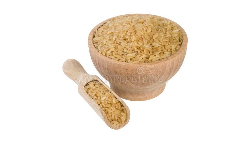 Καφετί ρύζι στο ξύλινο κύπελλο και σέσουλα που απομονώνεται στο άσπρο υπόβαθρο διατροφή βιο φυσικό συστατικό τροφίμων στοκ εικόνα