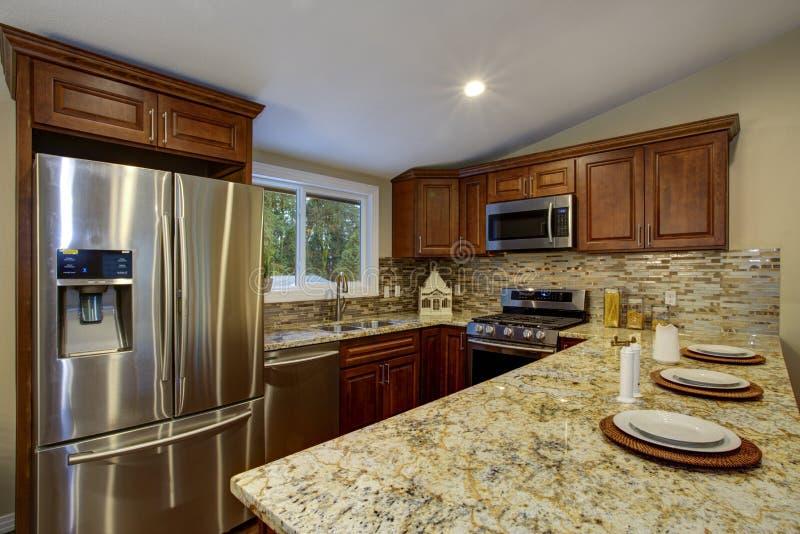 Καφετί σχέδιο κουζινών με τα γραφεία κουζινών μαονιού στοκ φωτογραφία με δικαίωμα ελεύθερης χρήσης