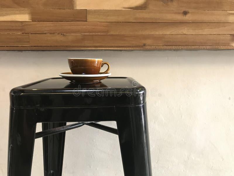 Καφετί φλυτζάνι του καυτού καφέ με το πιατάκι στο μαύρο σκαμνί φραγμών μετάλλων στοκ φωτογραφία